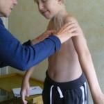 Augusti 2010. En månad senare. På barnhabiliteringen. Sjukgymnasten mäter vinklar. För att se hur mycket rörlighet Hugo har i alla leder.